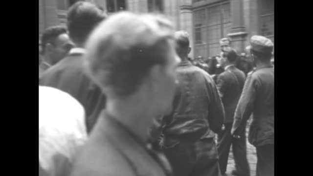 men and officers walking out of building passing people gathered in maybe courtyard / various shots pan men in courtyard with police behind them... - paramount building stock videos and b-roll footage
