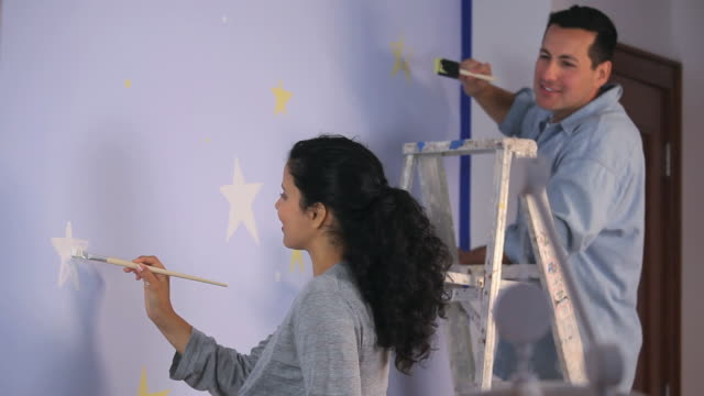 ms tu men and pregnant women painting stars on wall in nursery room / richmond, virginia, usa.   - nursery bedroom stock videos & royalty-free footage