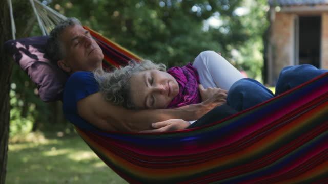 men and woman having a nap in a hammock. - eyes closed点の映像素材/bロール