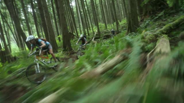 WS POV Men and woman mountain biking through forest / Squamish, British Columbia, Canada