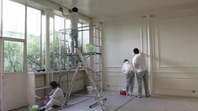 vídeos de stock e filmes b-roll de men and woman painting wall - pinta
