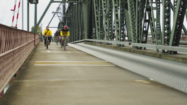 WS Men and woman riding bicycles on Hawthorne bridge / Portland, Oregon, USA