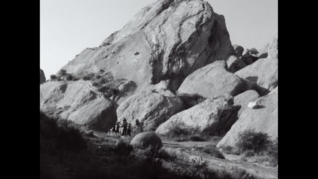 vidéos et rushes de ws pan men and woman riding horses in desert / united states - 1956