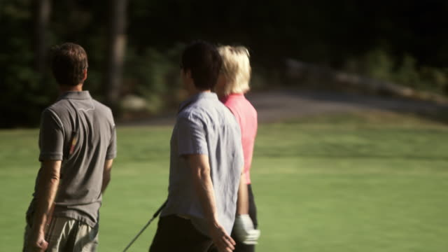 vidéos et rushes de ms ts r/f men and woman walking on golf course towards golf cart / squamish, british columbia, canada - golf