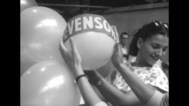 vidéos et rushes de men and women blow up balloons with machine at democratic national convention at the international amphitheatre in chicago / women tie balloons... - adlai stevenson