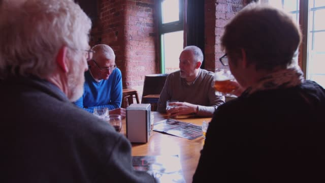 Men and Women Chatting Around Table in Pub