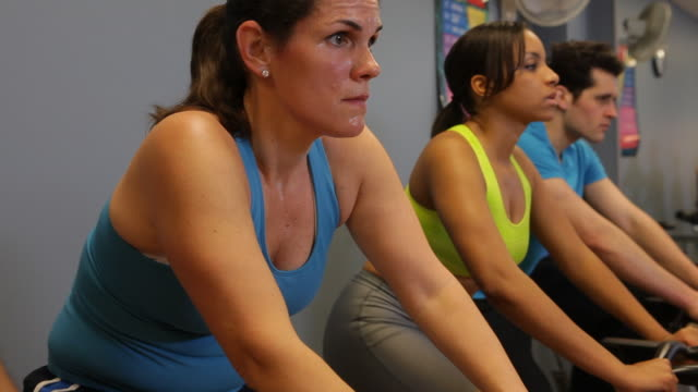 Men and women concentrate as they work out on exercise bikes.