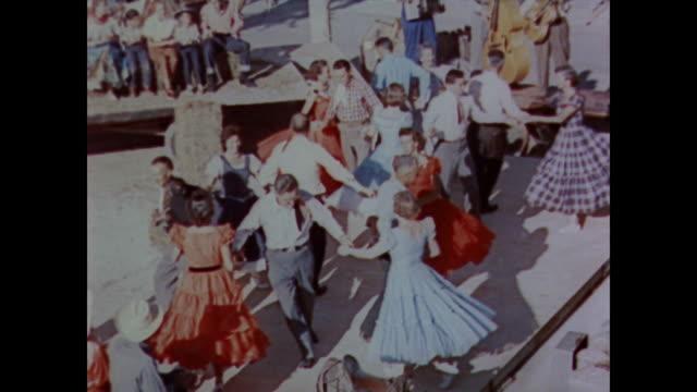vídeos de stock e filmes b-roll de 1958 men and women country dancing in the sunshine - dança quadrada