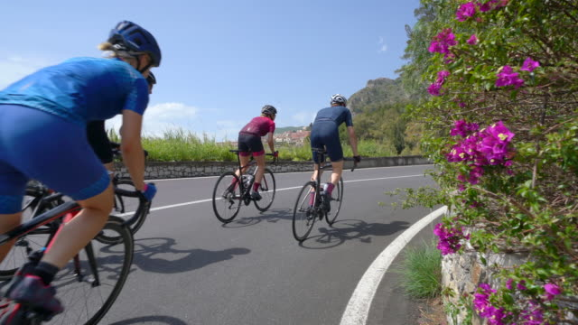 men and women couples cycling on bicycles, peloton riding on road bikes in italy. - プロトン点の映像素材/bロール