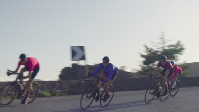 men and women couples cycling on bicycles, peloton riding on road bikes in italy. - ロードサイクリング点の映像素材/bロール
