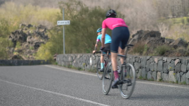 stockvideo's en b-roll-footage met men and women couples cycling on bicycles, riding on road bikes in italy. - twee personen