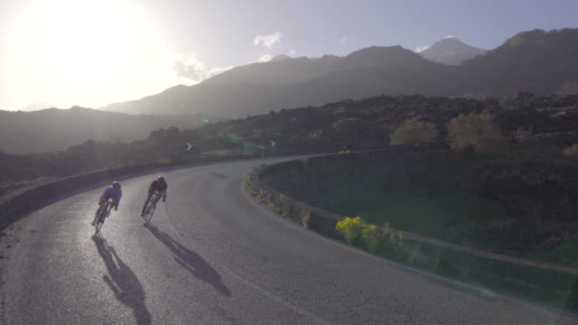 men and women couples cycling on bicycles, riding on road bikes in italy. - ロードサイクリング点の映像素材/bロール
