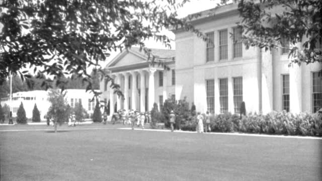 men and women cross a college campus and approach the main building. - 1935 stock videos & royalty-free footage