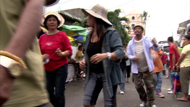 Men and women dance through a street in Manila during the Obando Fertility Festival. Available in HD.