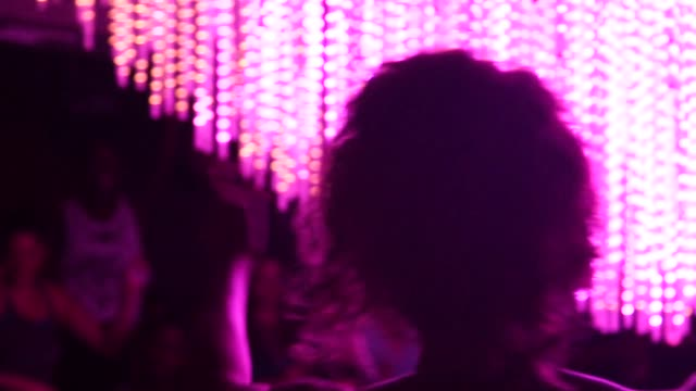 Men and women dancing at a daybreaker event in New York New York US on August 15 Close up of a womens silhouette dancing with flashing lights in the...