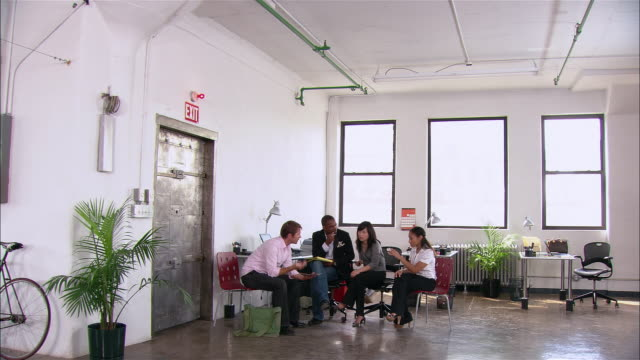 Men and women engaged in informal presentation or meeting in loft office / New York City