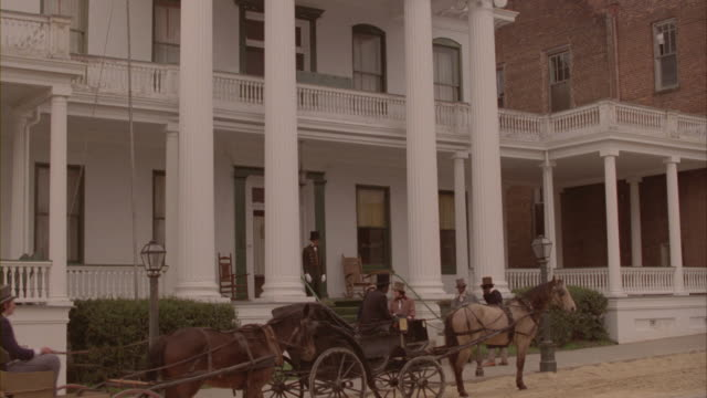 Men and women enter a Greek revival plantation house where a horse-drawn carriage and driver wait.