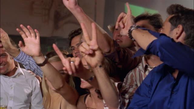 vídeos de stock e filmes b-roll de men and women gesture and order drinks at a crowded bar. - encomendar