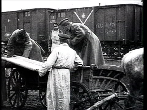 1915 b/w ms men and women helping wounded soldier onto stretcher from horse-drawn cart/ russia - prima guerra mondiale video stock e b–roll