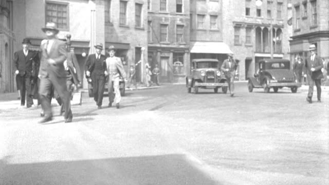 stockvideo's en b-roll-footage met men and women hurriedly cross a city street in 1935. - 1935