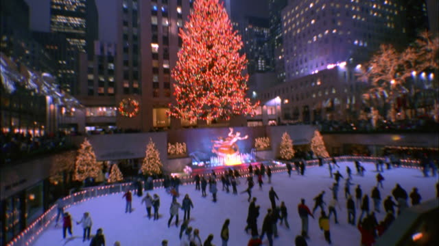 men and women ice skate at rockefeller center during the christmas holiday season. available in hd. - rockefeller center christmas tree stock videos & royalty-free footage