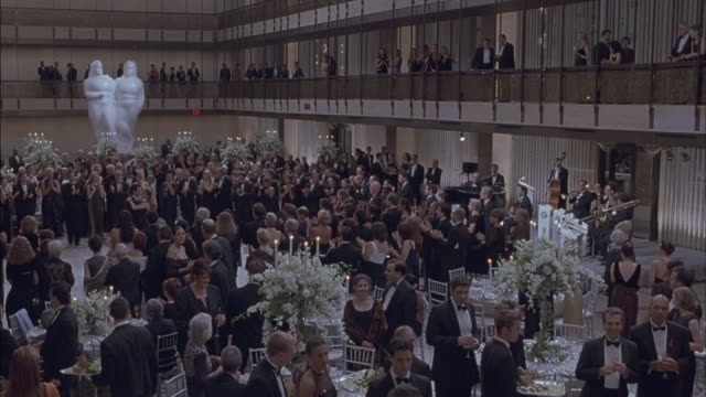 Men and women in a ballroom applaud.