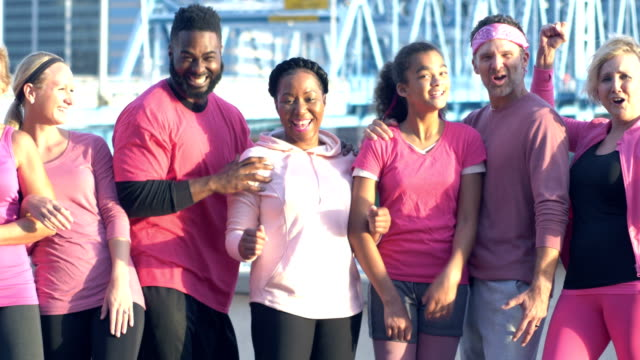 men and women in pink at breast cancer awareness event - 45 49 years stock videos & royalty-free footage