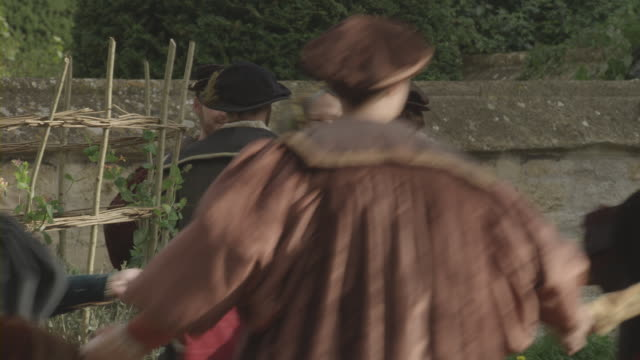 men and women in renaissance clothing dancing in a courtyard. - renaissance stock-videos und b-roll-filmmaterial