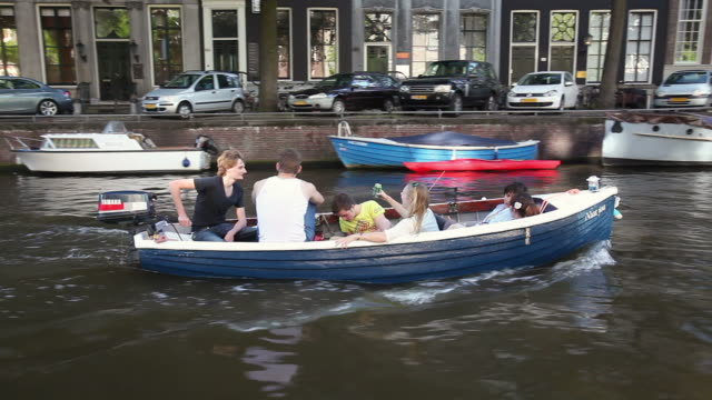 ws pov men and women in small motor boat moving through canal / amsterdam, the netherlands, holland - canal stock videos & royalty-free footage