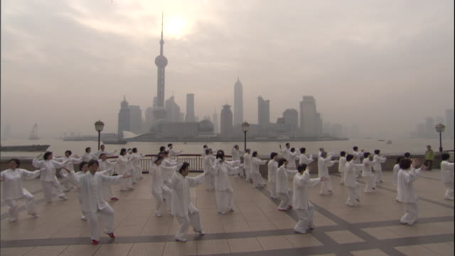 vídeos de stock e filmes b-roll de ha ws pan men and women in white uniforms practicing tai chi on waterfront / china - artes marciais
