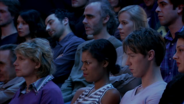 Men and women intensely watching suspenseful movie in theatre