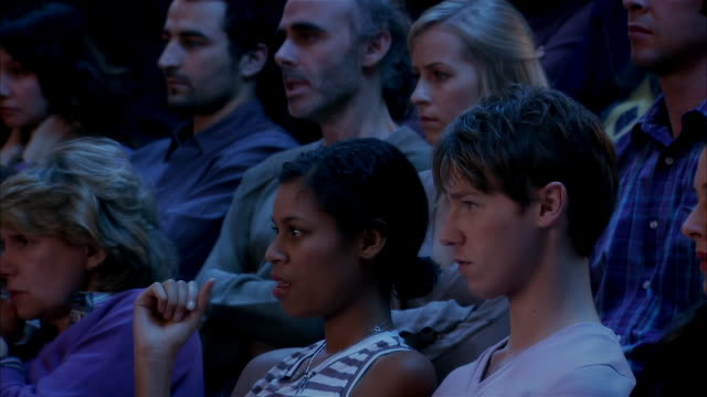 men and women intensely watching suspenseful movie in theatre - uncomfortable stock videos & royalty-free footage