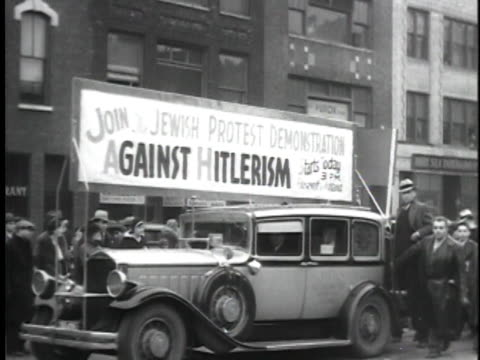 men and women marching on roosevelt avenue, some carrying signs, car with sign stating 'join the jewish protest demonstration against hitlerism.' - ユダヤ教点の映像素材/bロール