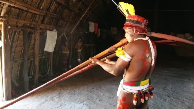men and women of the kamayura tribe play music and dance announcing the coming of the annual kuarup festival, shot on june 11th, 2014. - indigenous culture stock videos & royalty-free footage