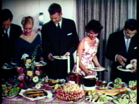 1953 MONTAGE men and women placing food on places at a buffet dinner party / AUDIO