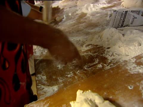 vídeos de stock, filmes e b-roll de men and women roll out dough at a large table - rolo de pastel
