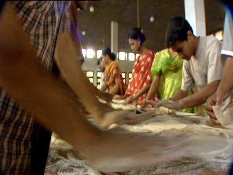 vídeos de stock, filmes e b-roll de men and women roll out dough at a table - rolo de pastel