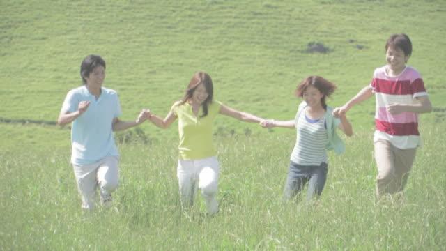 Men and women running hand in hand in green