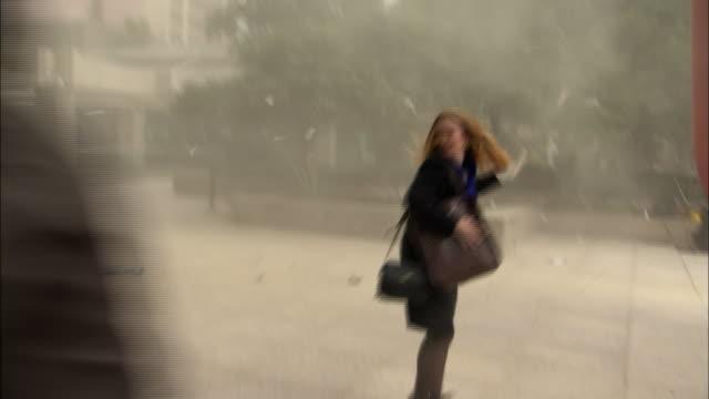 men and women rush into a building fleeing a storm. - dammstorm storm bildbanksvideor och videomaterial från bakom kulisserna