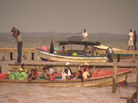 Men and women sit in boats that bob gently on a river in Honduras