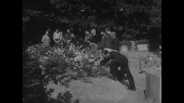 ms men and women standing at large grave with lots of flowers on it / cu flowers and banner / pan men and women standing graveside with heads bowed /... - grab stock-videos und b-roll-filmmaterial