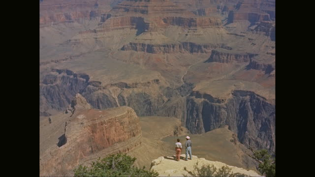 WS Men and women standing on cliff and looking at view of Grand Canyon / United States