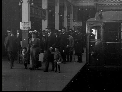 1905 B/W WS Men and women standing on platform in Grand Central Station as Interborough Subway train starts to leave / New York, New York, USA