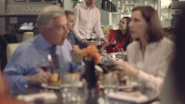 vídeos de stock, filmes e b-roll de ms r/f homens e mulheres conversando em restaurante, garçom servindo comida - camisa e gravata