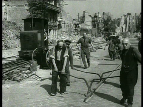 men and women use pickaxes and shovels to clean up the remains of destroyed houses and buildings to make the transport of the debris easier they made... - 1947 stock-videos und b-roll-filmmaterial