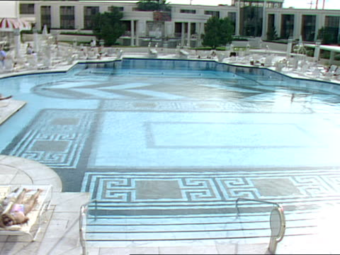 men and women walk and sunbath near a pool at caesars palace - zurücklehnen stock-videos und b-roll-filmmaterial