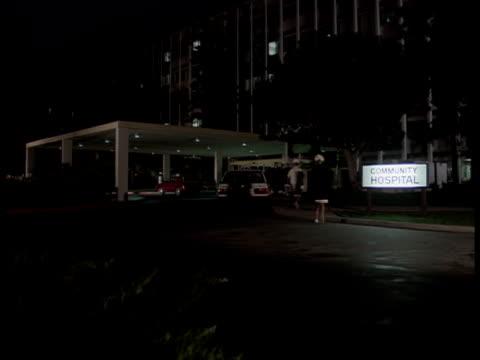 vídeos de stock, filmes e b-roll de men and women walk into a hospital entrance at night. - visita
