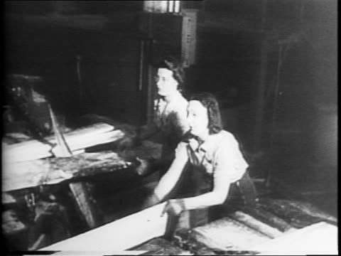 Men and women walking into Weyerhauser Timber Company sawmill / montage of women positioning boards for cutting / women storing cut lumber / woman...