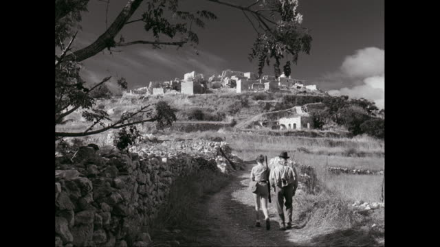 WS Men and women walking on dirt road with town in background / United States