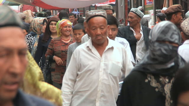 slo mo ms men and women walking through sunday market / kashgar, xinjiang, china - 新疆ウイグル自治区点の映像素材/bロール